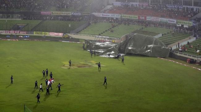 Bangladeshi ground staff cover the field as rain falls before the Asia Cup T20 cricket tournament final match between Bangladesh and India at the Sher-e-Bangla National Cricket Stadium in Dhaka on March 6, 2016. / AFP / MUNIR UZ ZAMAN        (Photo credit should read MUNIR UZ ZAMAN/AFP/Getty Images)