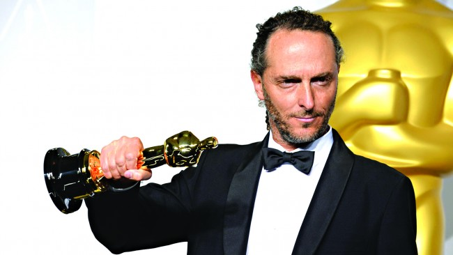 """Emmanuel Lubezki poses in the press room with the award for best cinematographer of the year for """"Gravity"""" during the Oscars at the Dolby Theatre on Sunday, March 2, 2014, in Los Angeles. (Photo by Jordan Strauss/Invision/AP)"""