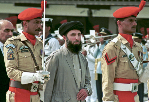 FILE - In this Wednesday, June 26, 1996 file photo, Gulbuddin  Hekmatyar, center, passes in front of an honor guard in the Afghan capital of Kabul, Afghanistan.  A representative of a notorious Afghan warlord says he has dropped a key condition for ending his war on the Afghan state and wants a peace treaty with Kabul.  (AP Photo, File)